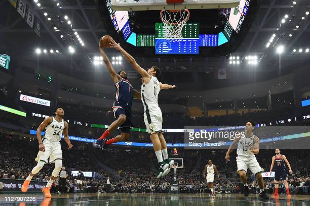 Brook Lopez of the Milwaukee Bucks blocks a shot by Trevor Ariza of the Washington Wizards during the first half of a game at Fiserv Forum on...