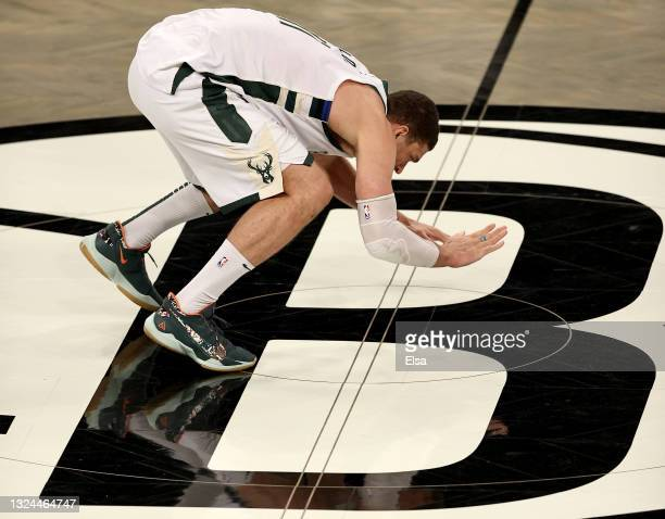 Brook Lopez of the Milwaukee Bucks celebrates the win by hitting the Brooklyn Nets logo during game seven of the Eastern Conference second round at...