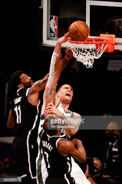 Brook Lopez of the Milwaukee Bucks dunks between Kyrie Irving and Kevin Durant of the Brooklyn Nets during the third quarter during Game One of the...