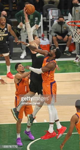 Brook Lopez of the Milwaukee Bucks goes up for a dunk over Devin Booker and Deandre Ayton of the Phoenix Suns at Fiserv Forum on July 20, 2021 in...