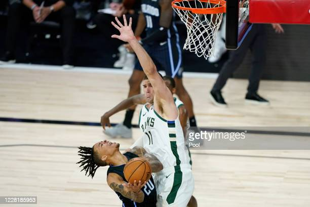 Brook Lopez of the Milwaukee Bucks tries to block a shot by Markelle Fultz of the Orlando Magic in the first half of Game Four during the first round...