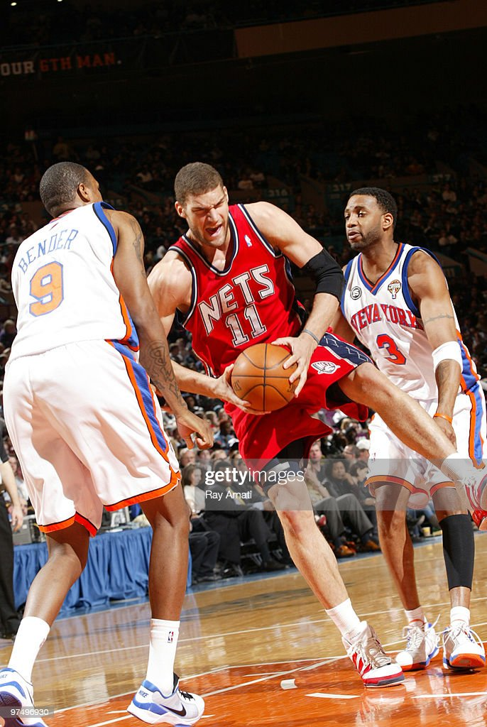 Brook Lopez #11 of the New Jersey Nets rebounds against Jonathan Bender #9 and Tracy McGrady #3 of the New York Knicks on March 6, 2010 at Madison Square Garden in New York City.