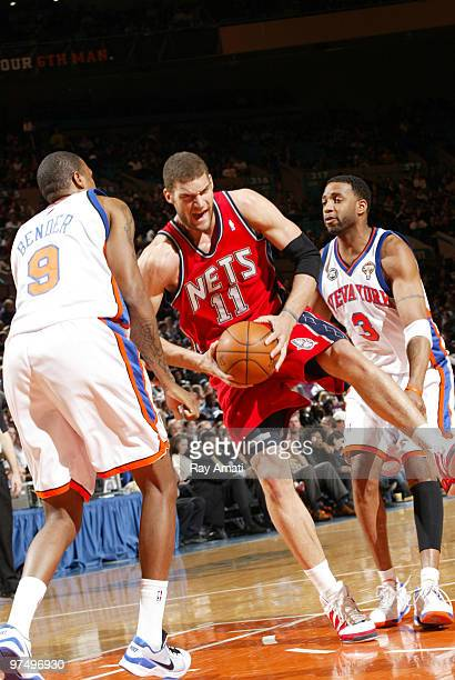 Brook Lopez of the New Jersey Nets rebounds against Jonathan Bender and Tracy McGrady of the New York Knicks on March 6 2010 at Madison Square Garden...