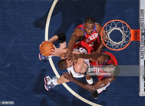 Brook Lopez of the New Jersey Nets shoots against Elton Brand and Samuel Dalembert of the Philadelphia 76ers during the game on November 11 2009 at...