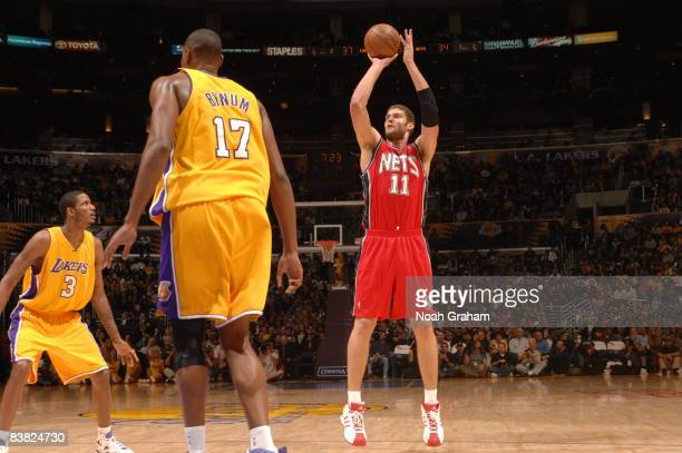 Brook Lopez of the New Jersey Nets shoots while Trevor Ariza and Andrew Bynum of the Los Angeles Lakers look on during their game at Staples Center...