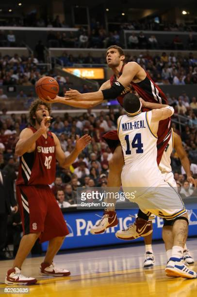 Brook Lopez of the Stanford Cardinal drives to the basket against the defense of Lorenzo Mata-Real of the UCLA Bruins during the championship game of...