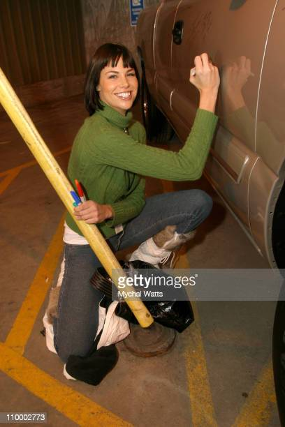 Brooke Burns autographs a 2005 Chevrolet Silverado Pickup which General Motors will donate to the National Ability Center a local charity organization