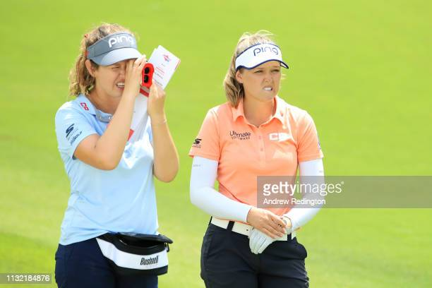 Brooke Henderson of Canada and her sister caddie Brittany Henderson look on during a practice round prior to the HSBC Women's World Championship at...