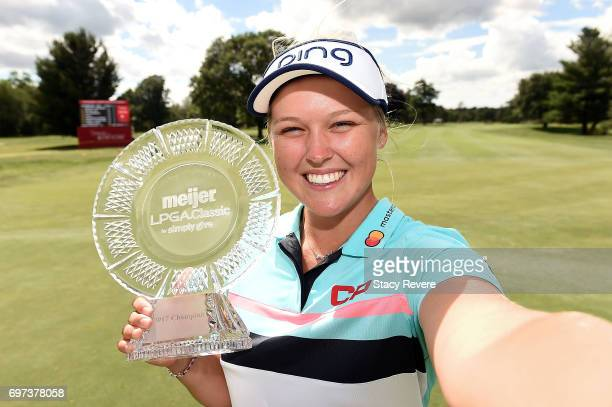 Brooke Henderson of Canada imitates a selfie as she poses with the championship trophy during the final round of the Meijer LPGA Classic at...