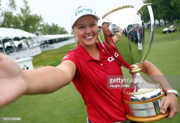 Brooke Henderson of Canada imitates a 'selfie' with the champions trophy following the final round of the CP Womens Open at the Wascana Country Club...