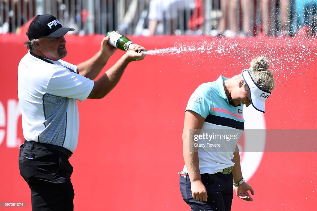 Brooke Henderson of Canada is sprayed with champagne by her father Dave Henderson during the final round of the Meijer LPGA Classic at Blythefield Country Club on June 18, 2017 in Grand Rapids, Michigan.