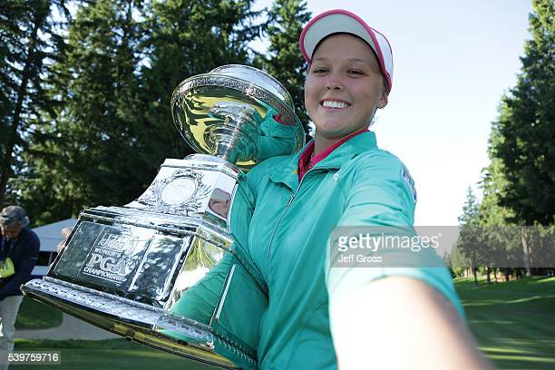 Brooke Henderson of Canada poses for a simulated selfie with the trophy after winning the KPMG Women's PGA Championship in a playoff against Lydia Ko...