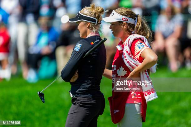 Brooke Henderson talks with her caddie/sister Brittany Henderson as they survey the green before her putt on the 14th hole during the first round of...