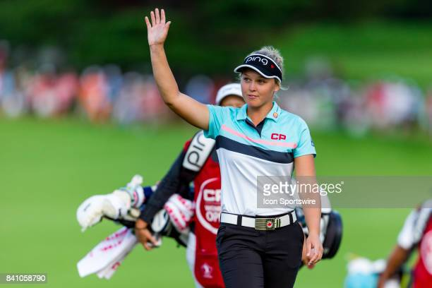 Brooke Henderson waves to the cheering crowd as she walks onto the green of the 18th hole during the final round of the Canadian Pacific Women's Open...