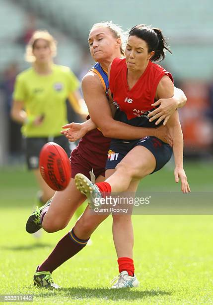 Brooke Lochland of Melbourne kicks whilst being tackled during the women's AFL exhibition match between Melbourne and Queensland at Melbourne Cricket...