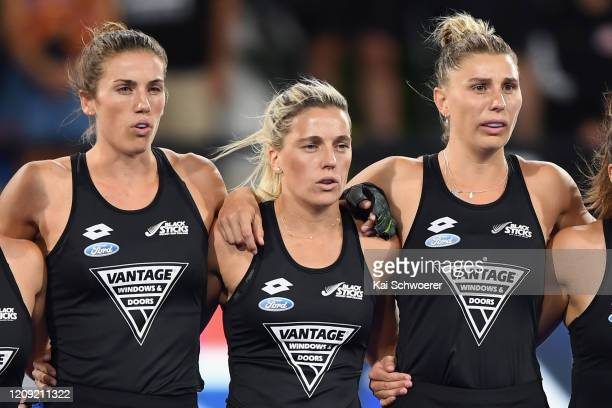 Brooke Neal, Gemma McCaw and Olivia Merry of New Zealand line up for their national anthem prior to the FIH Women's Pro League match between the New...