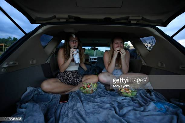 Brooke Shearer and Malayne Mingus eat popcorn while watching a movie in the back of a car at the Sauerbeck Family Drive-In on May 25, 2020 in La...
