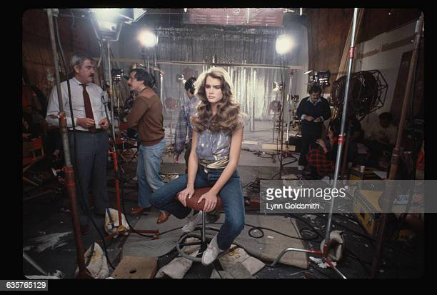 Brooke Shields sits on a set during the filming of a television commercial for Wella Balsam shampoo