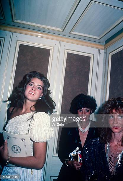 Brooke Shields wearing a white pleated formal dress in an elevator circa 1970 New York