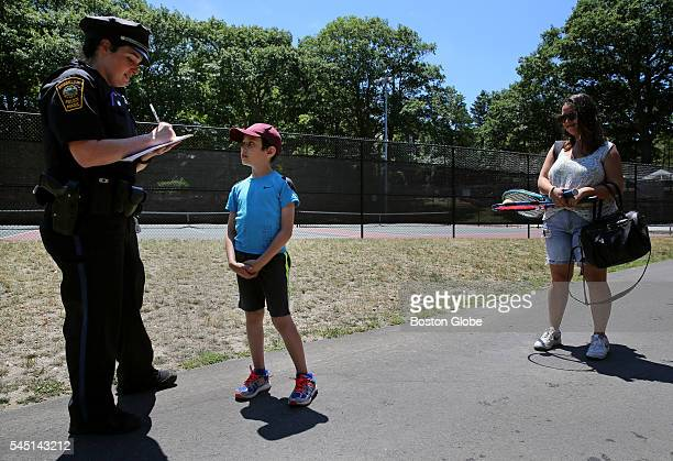 Brookline police officer Katie McCabe left gives a conehead citations to Daniel Leary while visiting Jean B Waldstein Park with his babysitter...