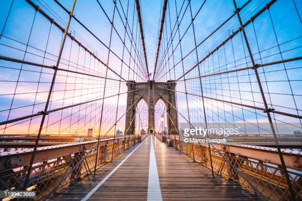 brooklyin bridge's pedestrian walkway at sunrise, new york city - brooklyn new york stock pictures, royalty-free photos & images