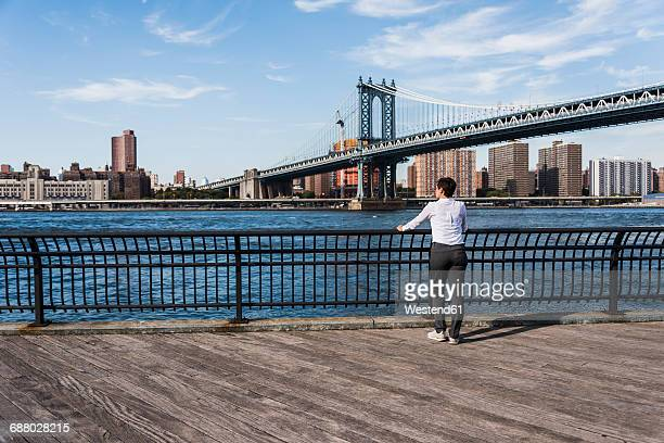 USA, Brooklyn, back view of businesswoman looking at East River