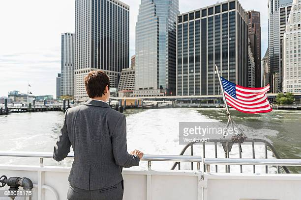 USA, Brooklyn, back view of businesswoman on a boat looking at Manhattan