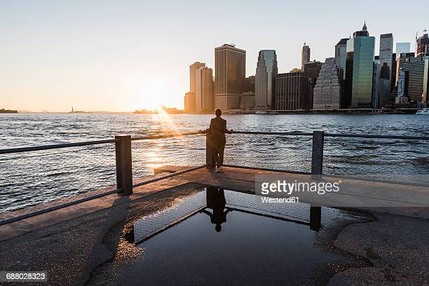 USA, Brooklyn, back view of woman leaning on railing looking at view at sunset