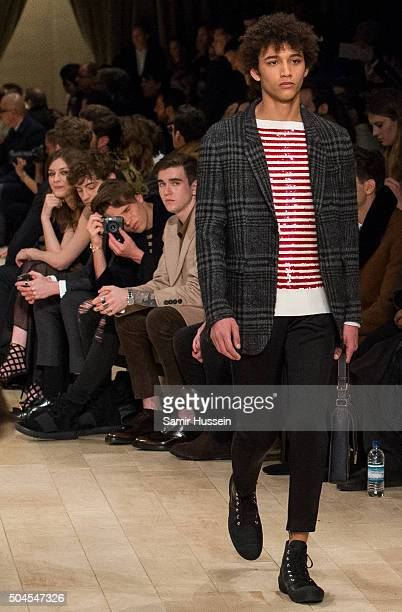 Brooklyn Beckham takes a photo as Gabriel DayLewis watches a model walk the runway at the Burberry show during The London Collections Men AW16 at...