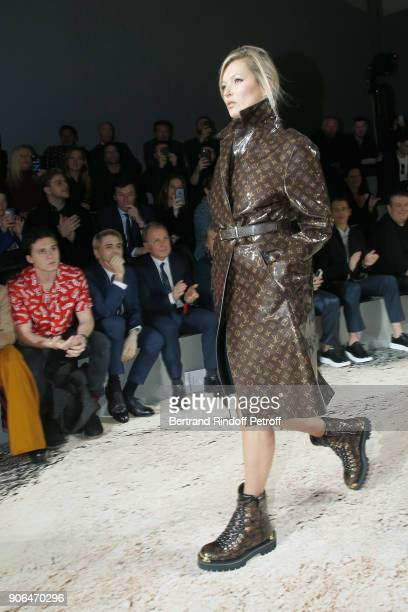 Brooklyn Beckham Xavier Dolan and CEO of Louis Vuitton Michael Burke watch Kate Moss walking the runway during the Louis Vuitton Menswear Fall/Winter...