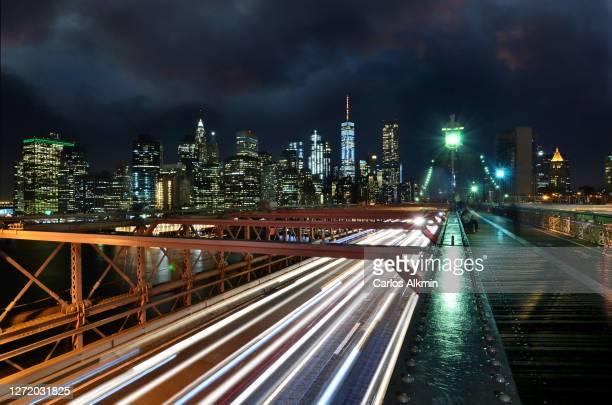 brooklyn bridge against illuminated skyline of manhattan - new york city - usa - carlos alkmin stock pictures, royalty-free photos & images