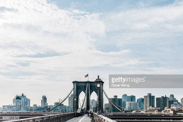 brooklyn bridge against new york cityscape - brooklyn bridge stock pictures, royalty-free photos & images