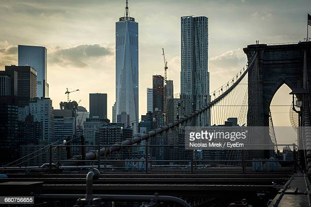 brooklyn bridge against one world trade center in city at dusk - world financial center new york city stock pictures, royalty-free photos & images