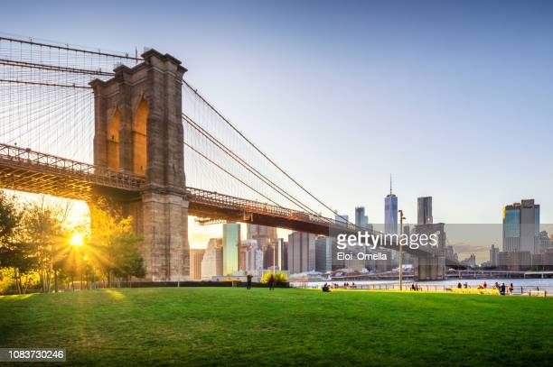 brooklyn bridge und manhattan bei sonnenuntergang. new york city - new york city stock-fotos und bilder