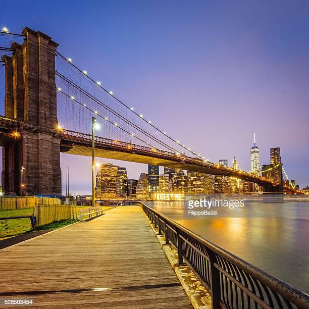 brooklyn bridge und manhattan bei sonnenuntergang - brooklyn bridge park stock-fotos und bilder