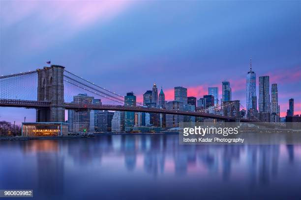 brooklyn bridge and manhattan skyline at sunset - ciudad de nueva york fotografías e imágenes de stock