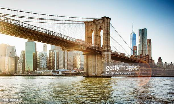 brooklyn bridge from east river sunset with flare - brooklyn bridge stock pictures, royalty-free photos & images