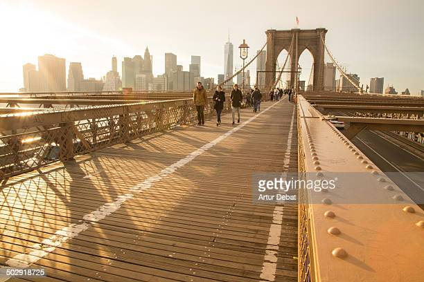 CONTENT] Brooklyn Bridge New York City Manhattan sunset ligh people person skyline skyscrapers sky iron wood construction engineering