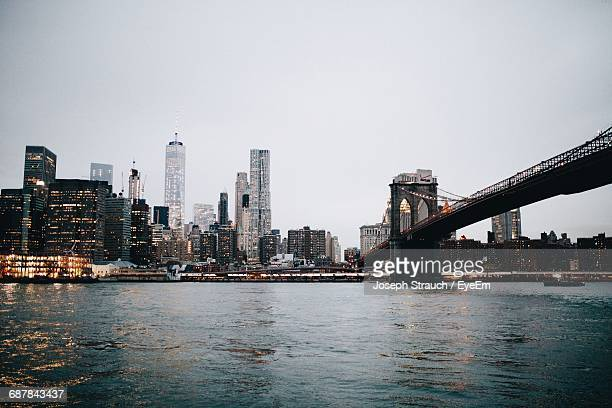 Brooklyn Bridge Over East River By Cityscape Against Clear Sky