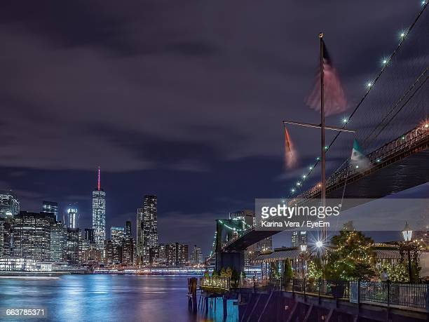 Brooklyn Bridge Over River Against Illuminated One World Trade Center In City