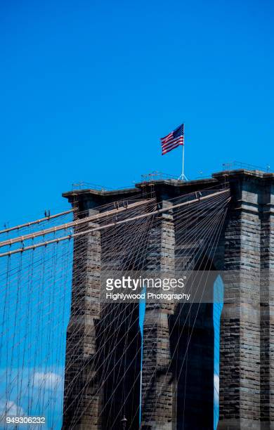 brooklyn bridge tower with us flag blowing in the summer wind on a clear day - highlywood fotografías e imágenes de stock