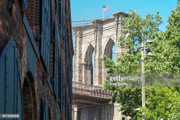 brooklyn bridge with warehouse windows - dumbo stock photos and pictures