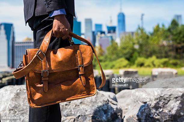 USA, Brooklyn, businessman with briefcase standing in front of Manhattan skyline, partial view