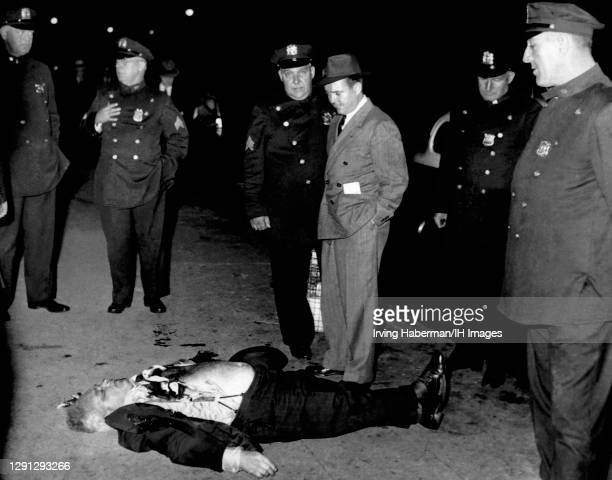 Brooklyn detectives and police officers inspect the wounds of the victim circa 1939 in Brooklyn, New York. Murder Inc. Is thought to have done the...