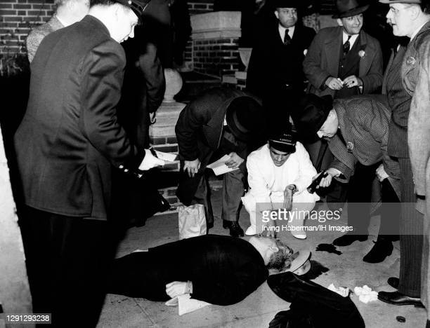 Brooklyn detectives and the doctor inspect the gun shot wound to the head of the victim circa 1939 in Brooklyn, New York. Murder Inc. Is thought to...