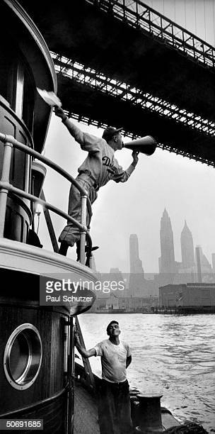 Brooklyn Dodger fan using megaphone while standing on tugboat's upper deck to announce his team's winning of the World Series as East River tugboat...