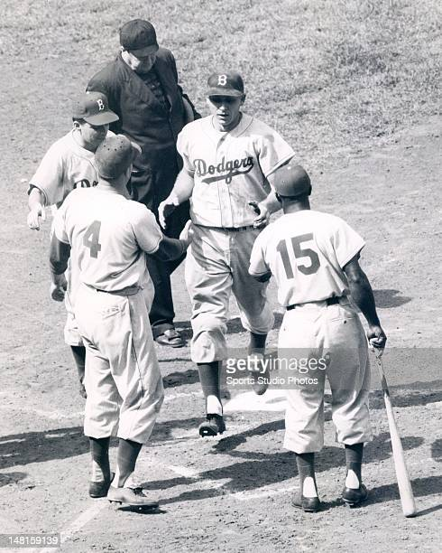 Brooklyn Dodger Gil Hodges being congratulated by teammates Duke Snider and Sandy Amoros after hitting a home run at Wrigley Field in Chicaco...