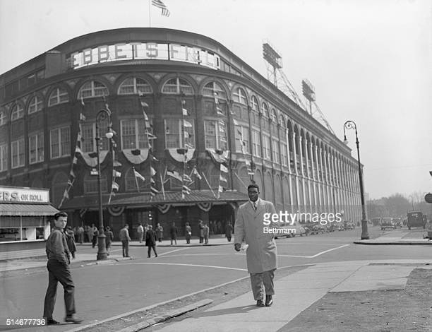 Brooklyn Dodgers baseball star Jackie Robinson walks on the sidewalk across the street from Ebbets Field, the Dodgers' home field. Robinson breaks...