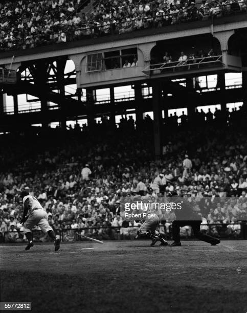 Brooklyn Dodgers batter Jackie Robinson bunts down the first base line as New York Yankees catcher Yogi Berra starts in pursuit during the 1955 World...