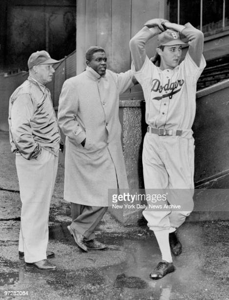 Brooklyn Dodgers' Billy Loes winds up as Chuck Dressen and Jackie Robinson during practice at the Polo Grounds in Brooklyn